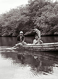 PANAMA, Panama Canal Zone, Barro Colorado, a man paddles a boat and a woman shades herself with a large leaf, Central America