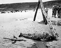 Crossed rifles in the sand are a comrade's tribute to this American soldier who sprang ashore from a landing barge and died at the barricades of Western Europe.  1944. (Coast Guard)<br /> Exact Date Shot Unknown<br /> NARA FILE #:  026-G-2397<br /> WAR &amp; CONFLICT BOOK #:  1044