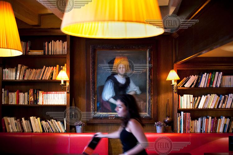 A woman walks past bookshelves at Les Editeurs Cafe in Paris.