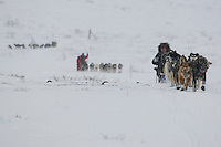 Sebastian Schnuelle runs ahead of Paul Gebhart and Rick Swenson in Ptarmigan Valley on their way to Rainy Pass shortly after leaving the Rainy Pass checkpoint in the Alaska Range on Monday.    Iditarod 2009