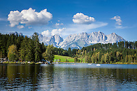 Austria, Tyrol, Reith near Kitzbuhel: idyllic Schwarzsee (Black Lake) on the outskirts of Kitzbuhel, at background Wilder Kaiser mountains | Oesterreich, Tirol, Reith bei Kitzbuehel: Schwarzsee, idyllisch gelegener Badesee, 8 ha gross und bis zu 8 m tief, einer der waermsten Seen der Alpen, im Hintergrund das Wilder Kaiser Gebirge
