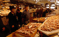 03 NOV 2003 - ATHENS, GRE - Visitors check the fish on sale on one of the stalls at the Central Market in Athens .(PHOTO (C) NIGEL FARROW)