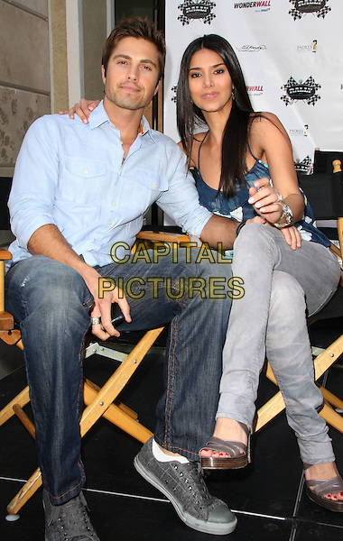 ERIC WINTER & ROSELYN SANCHEZ.Kids with Cancer Press Conference held at the Glendale Galleria, Glendale, California, USA..March 31st, 2009.full length blue shirt jeans denim grey gray pattern top married husband wife sitting.CAP/ADM/KB.©Kevan Brooks/AdMedia/Capital Pictures.