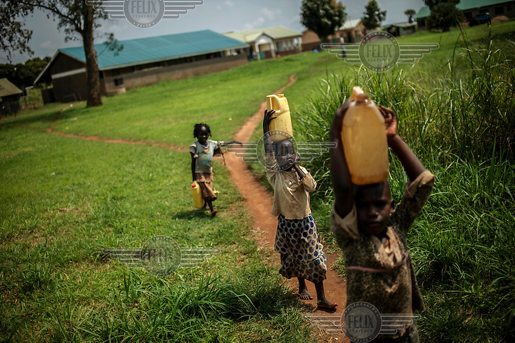 Children carry water pumped from a well on the grounds of the Atiak health clinic...