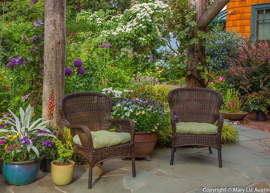 Vashon-Maury Island, WA Outdoor seating area with wicker chairs, colorful pots and perennial garden.