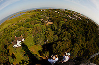 Visitors enjoy the view from Currituck Beach Lighthouse, one of the few North Carolina coastal lighthouses that visitors can climb to the top. Currituck Light is located on the Outer Banks in Corolla, North Carolina. With its red brick exterior, the lighthouse is  an example of Gothic Revival architecture. Located in the town of Corolla, the Currituck Beach Light was the last of four beacons placed at intervals from Cape Henry, Virginia to Cape Hatteras. Like other lighthouses on the North Carolina coast, the Corolla Lighthouse / Currituck Beach Lighthouse still aids ships in navigation. Charlotte NC photographer Patrick Schneider has extensive photo collections of the following lighthouses: Bodie Island Lighthouse, Bald Head Island Lighthouse, Cape Fear Lighthouse, Cape Hatteras Lighthouse, Cape Lookout Lighthouse, Currituck Beach Lighthouse, Diamond Shoal Lighthouse, Federal Point Lighthouse, Oak Island Lighthouse, and Ocracoke Lighthouse on Ocracoke Island.