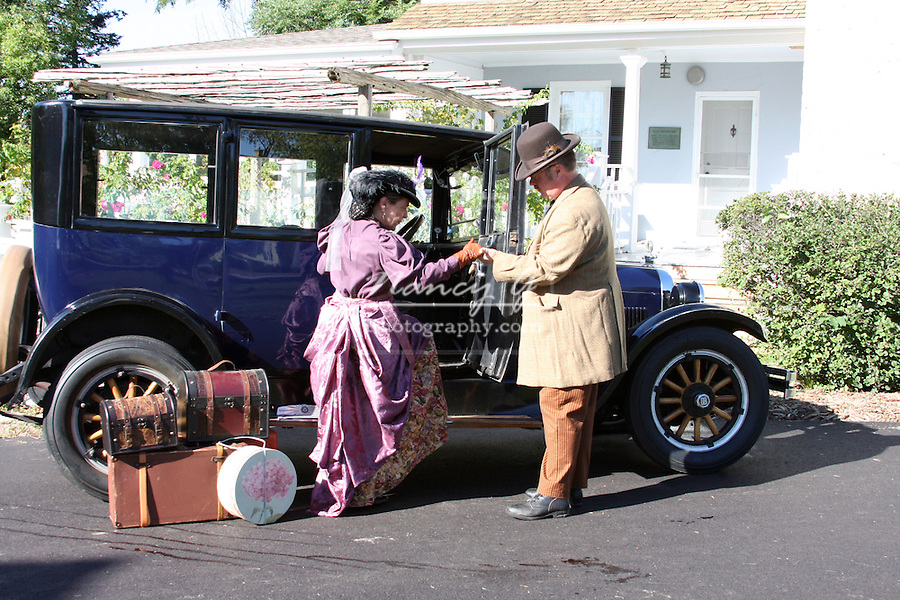 A gentleman helping a lady into the 1925 Dodge Brothers automobile