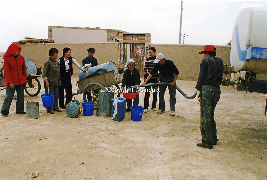 Local residents queue as a government truck provides water to villagers in Minqin County, Gansu Province, their local well is dry by 8 am each morning and not able to provide water until the following morning.  the Government water supply is lifeline to these 5,000 villagers. The moving sand and encroaching desert is so bad in this part of china that many of the roads have been swamped with sand and the wells have dried up. it is estimated that 3,900 kilometers square turn into desert each year. China is suffereing from severe water shortages with just 7% of the world's water and over 205 of the population.