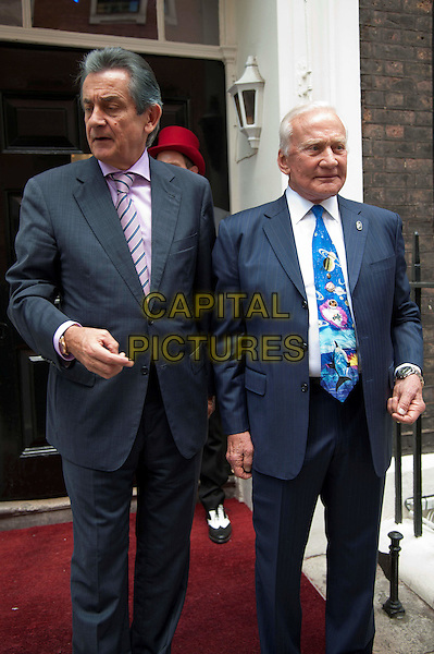 OMEGA President Stephen Urquhart & Buzz Aldrin .At Omega House for an Explore Space Q&A. Legendary American astronaut hosted a Q&A session.  House of St Barnabas, London, England..August 2nd, 2012.half length black blue suit tie print planets universe galaxy purple white shirt .CAP/BF.©Bob Fidgeon/Capital Pictures.