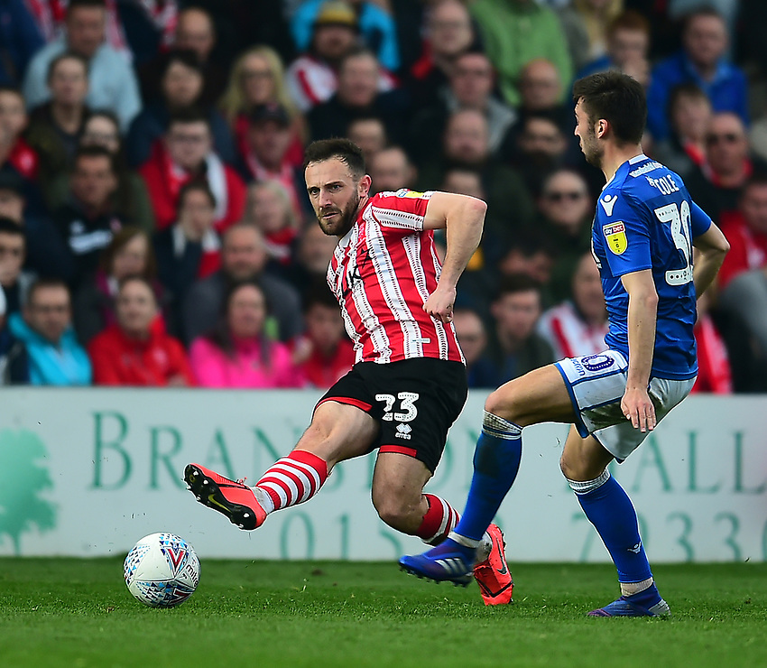 Lincoln City's Neal Eardley slides the ball past Macclesfield Town's Reece Cole<br /> <br /> Photographer Andrew Vaughan/CameraSport<br /> <br /> The EFL Sky Bet League Two - Lincoln City v Macclesfield Town - Saturday 30th March 2019 - Sincil Bank - Lincoln<br /> <br /> World Copyright © 2019 CameraSport. All rights reserved. 43 Linden Ave. Countesthorpe. Leicester. England. LE8 5PG - Tel: +44 (0) 116 277 4147 - admin@camerasport.com - www.camerasport.com