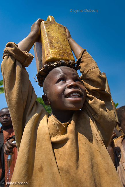 Tiyerive Rukundorwra, 8, carries home a heavy jerry can filled with clean water from one of the wells the Gazelles built in the Songa area of Burundi, Gilbert Tuhabonye's home area. Tiyerive fetches water a few times a day and is happy he has to walk less than a mile now.