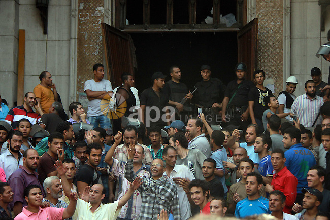 Egyptians security forces escort Islamist supporters of the Muslim Brotherhood out of the al-Fatah mosque, after hundreds of Islamist protesters barricaded themselves inside the mosque overnight, following a day of fierce street battles that left scores of people dead, near Ramses Square in downtown Cairo, Egypt, Saturday, Aug. 17, 2013. Authorities say police in Cairo are negotiating with people barricaded in a mosque and promising them safe passage if they leave. Muslim Brotherhood supporters of Egypt's ousted Islamist president are vowing to defy a state of emergency with new protests today, adding to the tension. Photo by Ahmed Asad