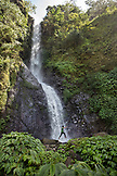INDONESIA, Flores, a boy trys to stay dry and not get his feet wet, Murukeba Waterfall in Waturaka Village