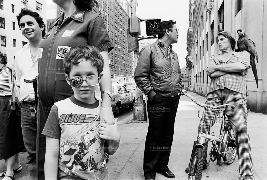 "USA. New York City. Life on the street. A boy with funky glasses wears a GI Joe T-shirt. Her mother wears work clothes with the logo of Esso ( petrol gas station) and a tiger. Put a tiger in your tank was a popular Esso advertising slogan. A woman seated on a bicycle has a parrot standing on her shoulder and talks to a man. Roas sign "" Don't walk"". G.I. Joe is a line of action figures produced by the toy company Hasbro. Although the members of the G.I. Joe team are not superheroes, they all had expertise in areas such as martial arts, weapons and explosives. Esso is an international trade name for ExxonMobil and its related companies. © 1986 Didier Ruef"