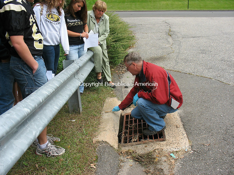 BEACON FALLS, CT - 3 October 2008 - 100308QL01 - While students from Woodland Regional High School in Beacon Falls watch, Lawrence K. Secor, senior environmental project manager with Nafis & Young of Northford, brushes off the top of a storm drain to affix a marker to educate the public on protection of waterways. More than 20 seniors with an Advance Placement enviromental science class at Woodland will volunteer to place the markers on storm drains throughout the town. Quannah Leonard Republican-American