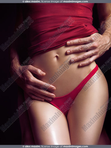 Sensual couple artistic photo. Man hands embracing young sexy woman in red underwear.
