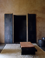 A pair of wooden interior doors in the living room are covered in metal for decorative effect