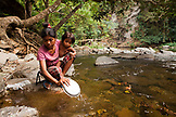 PHILIPPINES, Palawan, Barangay region, young Batak mother Diovina and daughter Lenilyn wash dishes in the stream in Kalakwasan Village