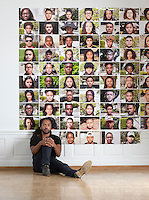 Cruz Riley '17 stands before photos he took of other students for his project, The Ninety-Five. His project presented color portraits of black students at Occidental College in clusters of five, dispersed at 19 locations all over campus. Photographed July 14, 2016 in the Weingart Hall Gallery for Occidental Magazine.<br />