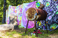 "A rusty barrel with ""flux"" engraved into it standing by some tye dye sheets."