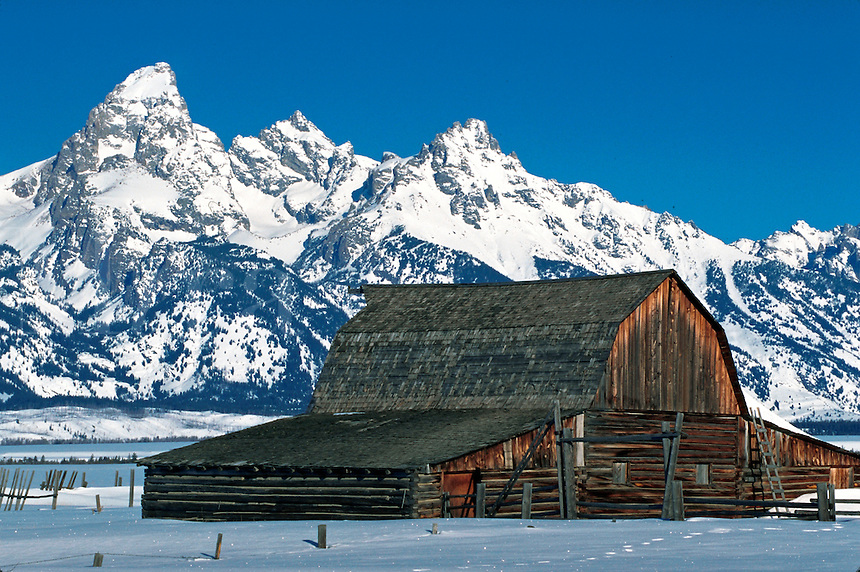 Winter scene of an old barn in foreground of Teton Mountain Range. Grand Teton National Park, Jackson Hole, Wyoming.