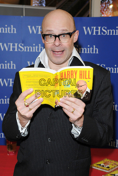 "Harry Hill .Signs copies of his new book ""A Complete History Of Tim"" at WH Smith, Lakeside Shopping Centre, Grays, Essex, England..10th December 2012.half length black suit jacket white shirt pinstripe glasses mouth open smiling books reading   .CAP/BRC.©Ben Rector/Capital Pictures."
