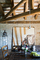 A large painting and a Moroccan lantern against an exposed brick wall behind the dining table