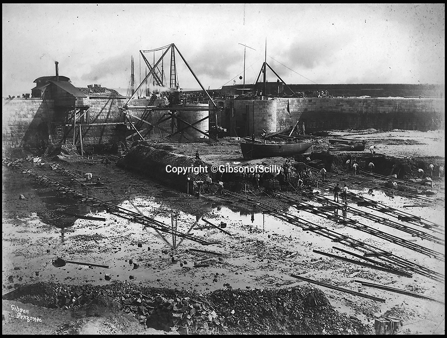 BNPS.co.uk (01202 558833)<br /> Pic: GibsonOfScilly/BNPS<br /> <br /> Inner dock being built at Penzanze.<br /> <br /> An archive of eye-opening photographs documenting the grim reality of Poldark's Cornwall has emerged for sale for &pound;25,000.<br /> <br /> More than 1,500 black and white images show the gritty lives lived by poverty-stricken families in late 19th and early 20th century Cornwall - around the same time that Winston Graham's famous Poldark novels were set.<br /> <br /> The collection reveals the lowly beginnings of towns like Rock, Fowey, Newquay and St Ives long before they became picture-postcard tourist hotspots.<br /> <br /> Images show young filth-covered children playing barefoot in squalid streets, impoverished families standing around outside the local tax office, and weather-beaten fishwives tending to the day's catch.<br /> <br /> The Cornish archive, comprising 1,200 original photographic prints and 300 glass negative plates, is tipped to fetch &pound;25,000 when it goes under the hammer as one lot at Penzance Auction House.