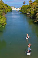 A man and woman standup paddleboarding on Anahulu Stream in Haleiwa, North Shore, O'ahu.