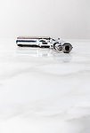 Handgun laying on marble surface pointing towards viewer