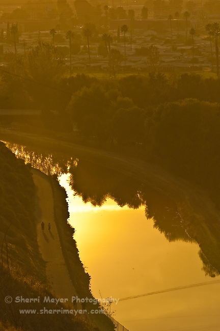 Cyclists riding along the canal below Panorama Park at sunset, Bakersfield, California.