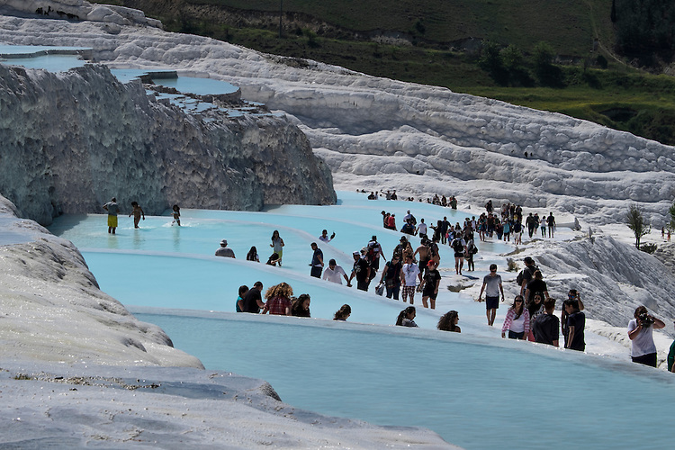 Overlooking the town of Pamukkale, the thermal spring terraces of Hierapolis descend in almost uniform stages.
