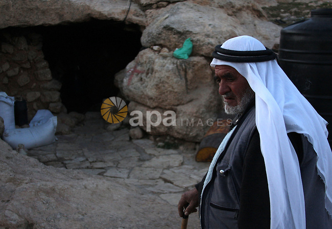 Palestinian man stands outside a cave in a mountainous area outside the city of Hebron in the occupied West Bank on May 22, 2010. Photo by Mamoun Wazwaz