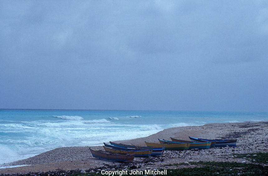 Fishing boats on a deserted, windswept, rocky beach, Barahona, Dominican Republic