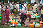 21 May 2013,  Gudageri Village, Karnartaka, India: Villagers wait to fill up their water jugs during the two hour window the taps run outside the Primary Health Care centre at Gudageri Village near Hubli. The World Bank is financing the Karnataka Health Systems Project that is bringing mobile health clinics to remote villages in Karnataka and covers the cost of an ambulance, a doctor, pharmacist, two nurses, a cleaner and a driver. Villagers have the opportunity to see a doctor once a week for basic services and will be referred to Primary Health Care centres for larger issues Picture by Graham Crouch/World Bank