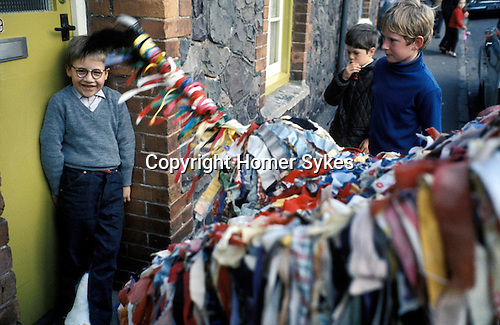 Minehead Hobby Horse Somerset. UK. Horse bows three times to young boy wearing old fashioned regulation National health spectacles.