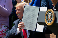 "United States President Donald J. Trump holds up a signed Executive Order ""to ensure that all faith-based communities have strong advocates in the White House"" during a National Day of Prayer event in the Rose Garden at the White House in Washington, DC on May 3, 2018. Credit: Alex Edelman / CNP /MediaPunch"