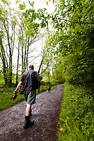 Dog walker near Pooh Bridge, Ashdown Forest, Sussex, UK, May 19, 2017. Picturesque Ashdown Forest stretches across the countries of Surrey, Sussex and Kent, and is the largest open access space in the South East of England. It is famous as the geographical inspiration for the Winnie the Pooh stories and is popular with fans of the characters.