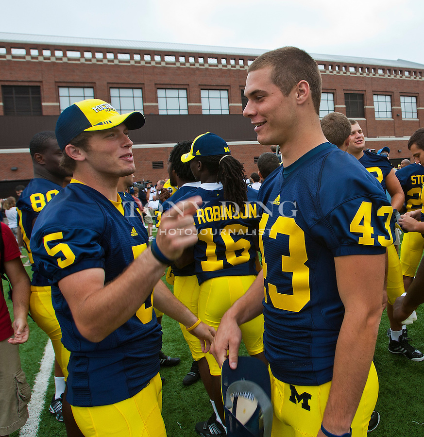 Michigan quarterback Tate Forcier (5) jokes with punter Will Hagerup (43) at the annual NCAA college football media day, Sunday, Aug. 22, 2010, in Ann Arbor, Mich. (AP Photo/Tony Ding)