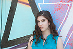 Portrait of a serious teenage girl with dark brown hair in front  of a mural in the East Village Arts District in Long Beach, CA, USA