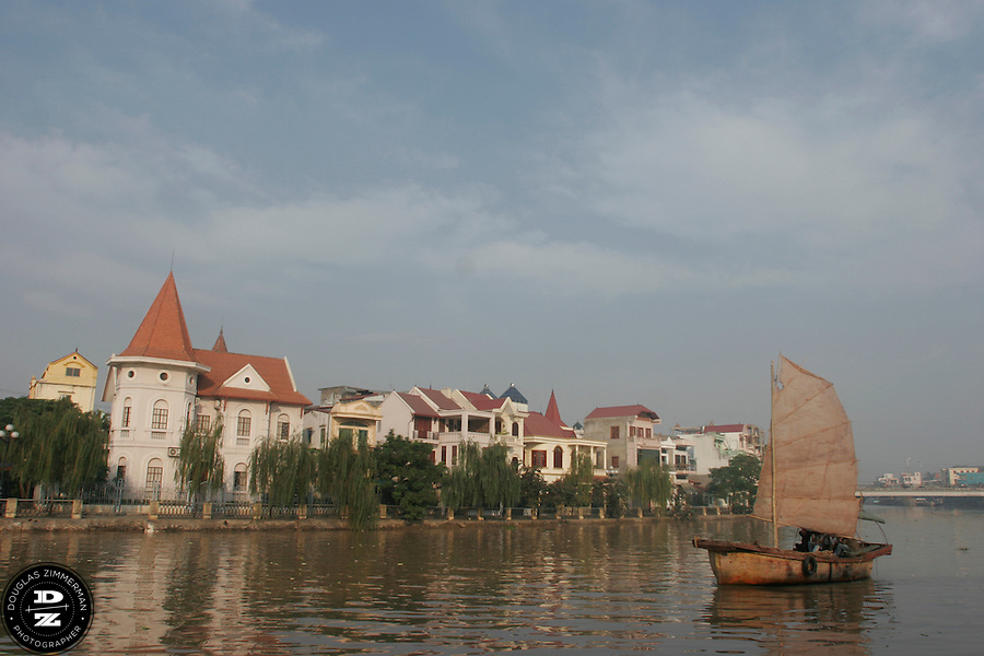 A traditional sailing boat cruises along the Tam Bac River in Haiphong, Vietnam.  Haiphong, the third largest city in Vietnam, is an important seaport and industrial center for the country.  Photograph by Douglas ZImmerman