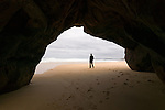 Framed by a cave, a man walks on the beach of Bordeira in the Algarve region of Portugal.