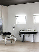 Two swivel windows are situated above the triple pedestal basin in this monochrome bathroom