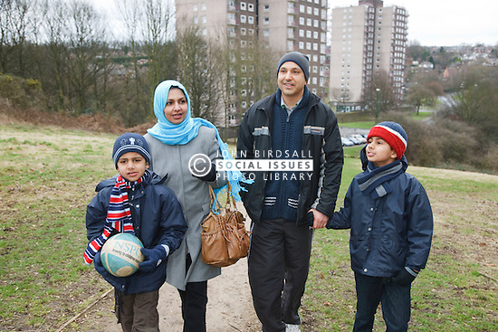 Asian family walking near tower blocks.