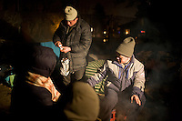 ROMANIA / Bucharest / 18.02.09..Chinese immigrants warm themselves around a fire across the street from the Chinese Embassy...Hundreds of Chinese immigrants are currently stuck in Romania after their work contracts with construction firms here were suddenly terminated in late January. They expected to make at least 800 Euros per month, or double what they can make in China as agricultural laborers. About 80 of them are camped out under plastic sheeting in front of the Chinese Embassy hoping to get some kind of help. During the day, hundreds more are joining them to stage a protest. They paid a Chinese broker 10,000 Euros a piece for the lucrative four year construction contracts and are hoping to get reimbursed in order to be able to buy tickets home. The immigrants are relying upon the help of generous Romanians who pull up and deliver food from their cars. The economic crisis hit Romania just as many of the immigrants arrived in November. ..© Davin Ellicson / Anzenberger