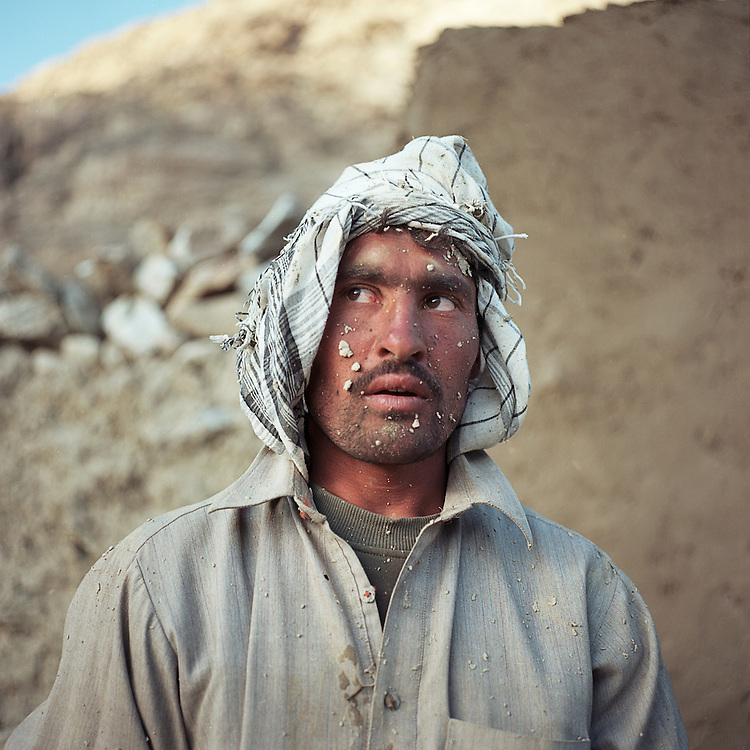 A man takes a break from building a mud brick house in the village of Ghaz Khan.