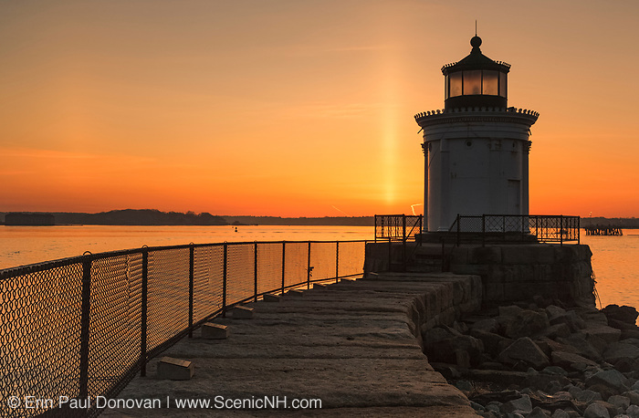 "Sunrise from Portland Breakwater Light in Portland, Maine USA during the spring months. The Portland Breakwater Light is also called the ""Bug Light"", and it is located at the entrance to Portland Harbor. It was designed after a Greek monument."