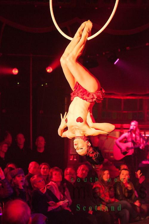 Big Burns Supper 2014, Dumfries, Le Haggis, almost naked female acrobat hanging upside down finely balance from a hoop suspended from the ceiling of the Spiegeltent,