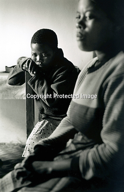 disiabu00053.Social Issues. Abuse. Bawinile Zulu, age 11, with her mother Tholakele a few days after the girl had been raped by a neighborÕs 22-year old son. An officer from the Child Protection Unit, a special police branch, that only handles crimes against children, is interviewing her..Before they called the police, the two families started negotiating the compensation, done traditionally here in Zulu culture in the rural areas. After receiving the cow, it was slaughtered and a feast for the whole village was held. Normally this occasion is a festive celebration but thereÕs not much singing and dancing that day. The 22-year old suspect was arrested by the police and is awaiting trial on January 27, 2002 in Port Shepstone, South Africa..©Per-Anders Pettersson/iAfrika Photos