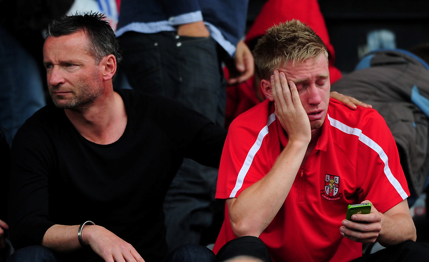 Former Lincoln City player Mark Hone, puts his arm round his son Lincoln's Danny Hone, right, sat in the Lincolnshire Echo Stand, who looks dejected at the end of the game as the Imps' relegation out of the Football League is confirmed<br /> <br /> Picture: Chris Vaughan/Lincolnshire Echo<br /> Requested: Sports Desk<br /> Job Title: Lincoln City Vs Aldershot Town<br /> Date: Saturday 7th May 2011<br /> Contact: Lincoln City Football Club on 01522 880011<br /> imps10<br /> LN5 8LD